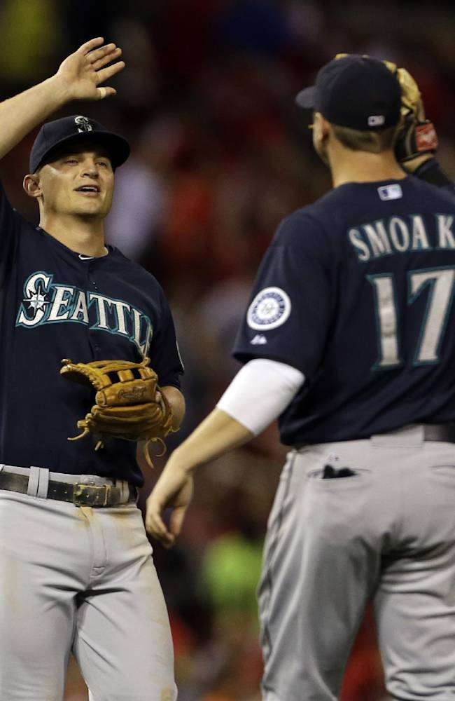 Seattle Mariners' Kyle Seager, left, and teammate Justin Smoak celebrate following the Mariners' 4-1 victory over St. Louis Cardinals in a baseball game Saturday, Sept. 14, 2013, in St. Louis