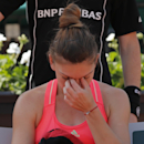 Romania's Simona Halep takes a break between games in the second round match of the French Open tennis tournament against Croatia's Mirjana Lucic-Baroni at the Roland Garros stadium, in Paris, France, Wednesday, May 27, 2015. Lucic-Baroni won in two sets 7-5, 6-1. (AP Photo/Christophe Ena)