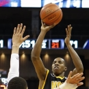 Virginia Commonwealth's Rob Brandenberg (11) shoots over Duquesne's Kadeem Pantophlet, left, in the second half of an NCAA college basketball game on Saturday, Jan. 19, 2013, in Pittsburgh. VCU won 90-63. (AP Photo/Keith Srakocic)