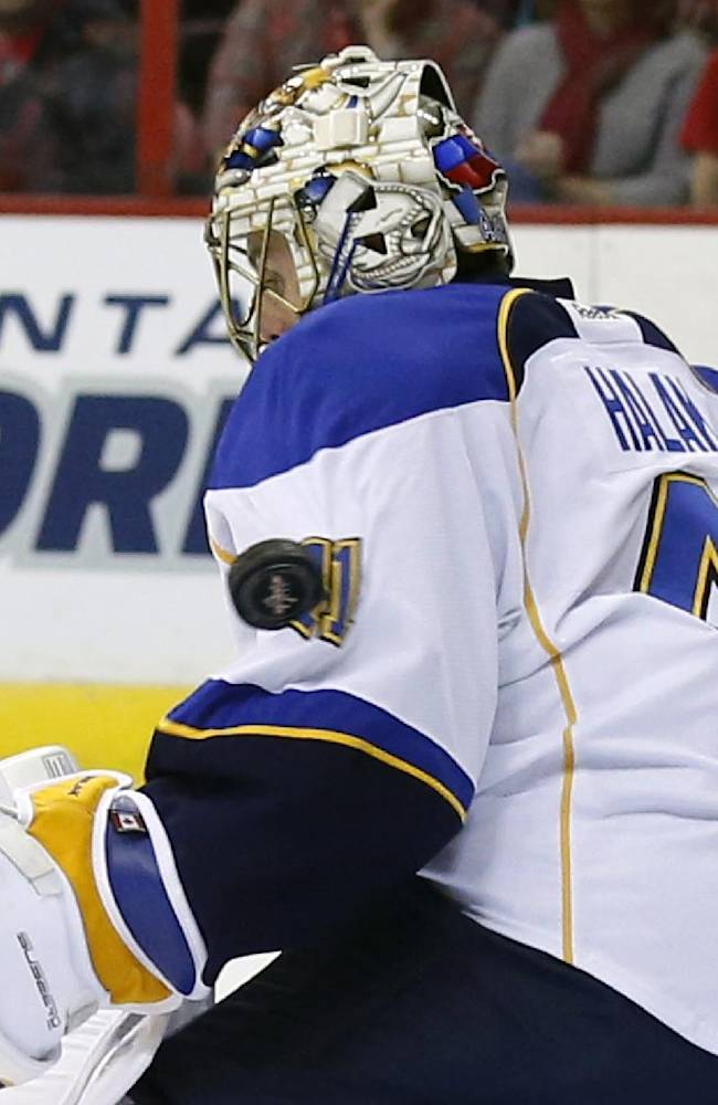 The puck bounces off the shoulder of St. Louis Blues goalie Jaroslav Halak (41) for a goal in the first period of an NHL hockey game against the Washington Capitals, Sunday, Nov. 17, 2013, in Washington