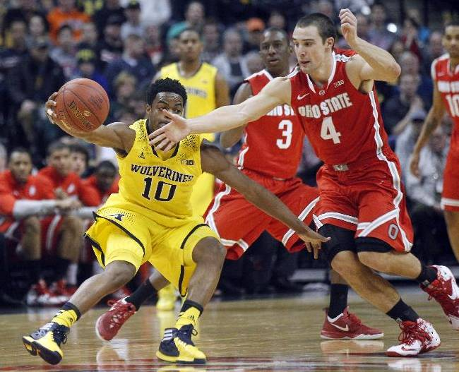 Michigan guard Derrick Walton Jr. (10) and Ohio State guard Aaron Craft (4) chase after a loose ball in the first half of an NCAA college basketball game in the semifinals of the Big Ten Conference tournament Saturday, March 15, 2014, in Indianapolis