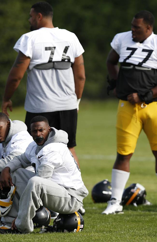 Pittsburgh Steelers' wide receiver Emmanuel Sanders, seated right, running back Isaac Redman, seated left, offensive tackle Mike Adams, standing left, and tackle Marcus Gilbert wait to start a practice session, at the Wasps rugby training ground, in London, Friday, Sept. 27, 2013. The Pittsburgh Steelers are to play the Minnesota Vikings in the NFL International Series at Wembley Stadium in London on Sunday, Sept 29