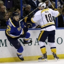 St. Louis Blues' Kevin Shattenkirk, left, is checked into the boards by Nashville Predators' James Neal during the first period of an NHL hockey game Saturday, Nov. 8, 2014, in St. Louis The Associated Press