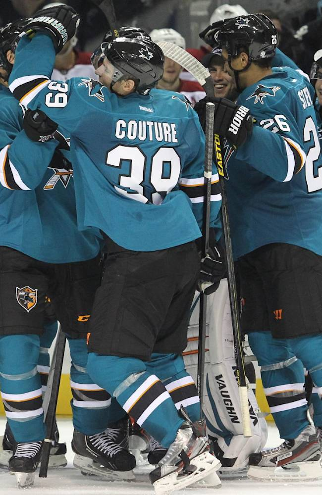 The Sharks' Logan Couture is congratulated by his teammates for his game-winning goal in overtime against the Coyotes during an NHL preseason hockey game in San Jose, Calif., Saturday, Sept. 21, 2013