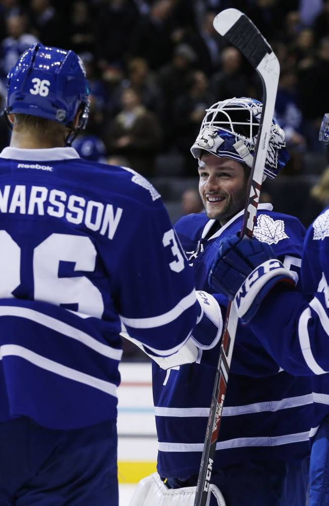 Toronto Maple Leafs' Carl Gunnarsson, Jonathan Bernier, and Morgan Rielly celebrate defeating the New York Islanders in an NHL hockey hockey game, Tuesday, Nov. 19, 2013 in Toronto
