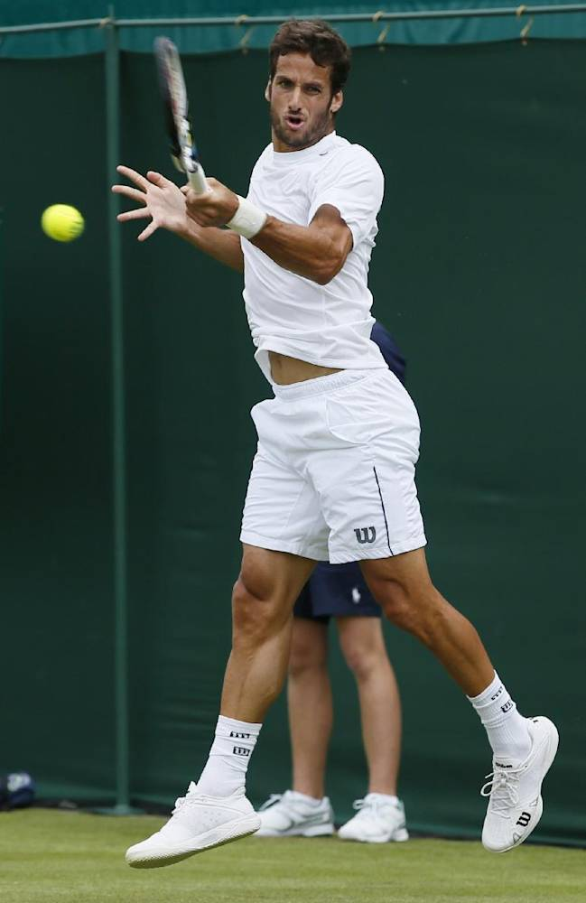Feliciano Lopez of Spain returns to Yuichi Sugita of Japan during their first round match at the All England Lawn Tennis Championships in Wimbledon, London, Tuesday, June 24, 2014