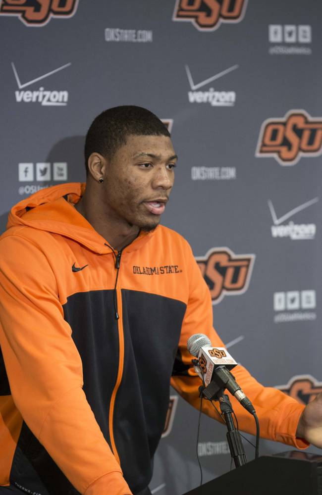 This photo provided by Oklahoma State University Athletics shows Oklahoma State basketball player Marcus Smart, left, addressing the media at a news conference in Stillwater, Okla., Sunday, Feb. 9, 2014, in regard to an altercation during an NCAA college basketball game the day before. Smart was suspended three games by the Big 12 for shoving a fan