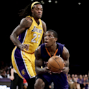 Phoenix Suns guard Eric Bledsoe, drives to the basket past Los Angeles Lakers center Jordan Hill during the second half of an NBA basketball game in Los Angeles, Tuesday, Dec. 10, 2013