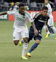 Portland Timbers forward Rodney Wallace, left, and Los Angeles Galaxy midfielder Hector Jimenez chase down the ball during the first half of an MLS soccer game in Portland, Ore., Sunday, Sept. 29, 2013. (AP Photo/Don Ryan)