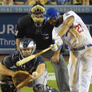 Los Angeles Dodgers' Matt Kemp, right, hits an RBI single to win the game as Atlanta Braves catcher Evan Gattis, left, and home plate umpire Hunter Wendelstedt look on during the 10th inning of a baseball game, Wednesday, July 30, 2014, in Los Angeles. (AP Photo/Mark J. Terrill)
