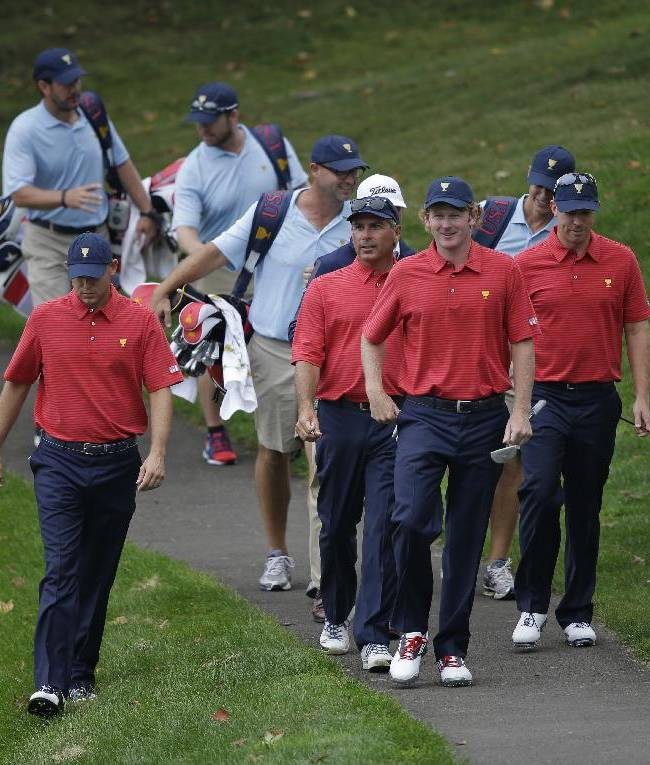 United States team captain Fred Couples, second from left in red shirt, walks with team players, from left, Bill Haas, Brandt Snedeker and Hunter Mahan to the 12th green during a practice round for the Presidents Cup golf tournament at Muirfield Village Golf Club Wednesday, Oct. 2, 2013, in Dublin, Ohio