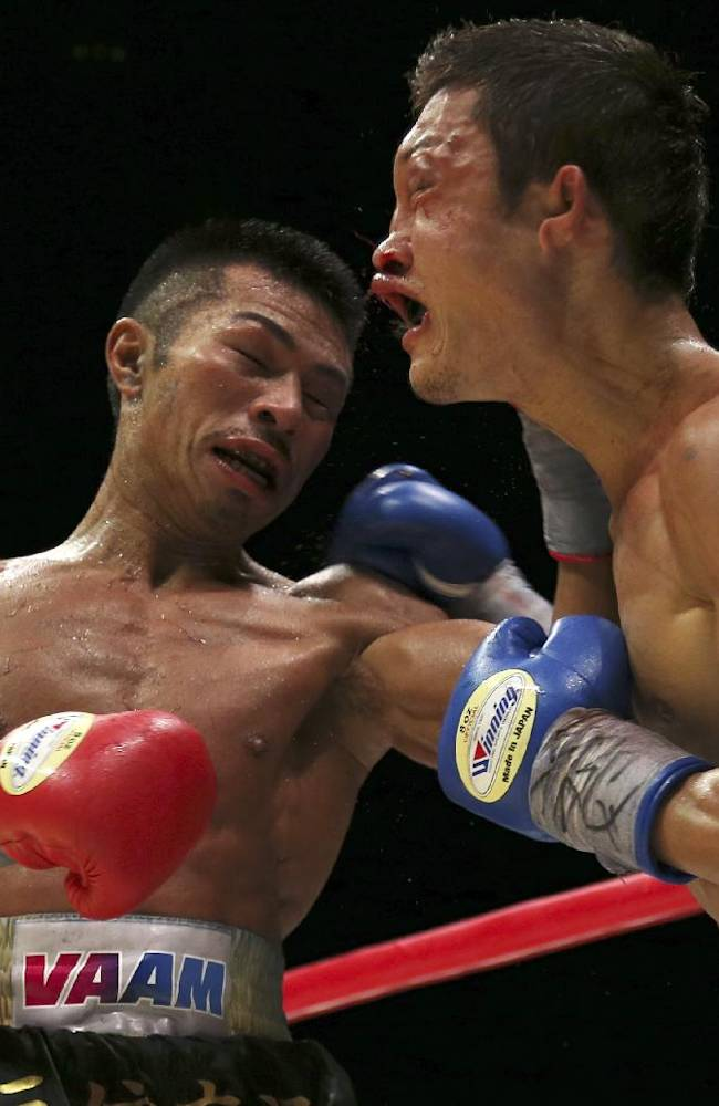 Japanese champion Takashi Uchiyama, left, sends a left to compatriot challenger Daiki Kaneko in the 11th round of their WBA super featherweight boxing title bout in Tokyo, Tuesday, Dec. 31, 2013. Uchiyama defended his title by a unanimous decision