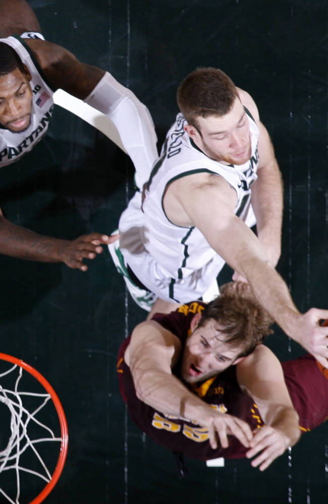 Michigan State's Matt Costello, center, controls a rebound against Minnesota's Elliot Eliason, bottom, as Michigan State's Branden Dawson, left, stands near during the second half of an NCAA college basketball game, Saturday, Jan. 11, 2014, in East Lansing, Mich. Michigan State won 87-75 in overtime