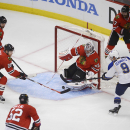 Chicago Blackhawks goalie Corey Crawford and right wing Ben Smith try to clear a shot by St. Louis Blues left wing Jaden Schwartz in the third period in Game 4 of a first-round NHL hockey playoff series in Chicago, Ill. on Wednesday, April 23, 2014. (AP