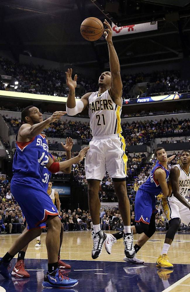 Indiana Pacers forward David West, right, shoots over Philadelphia 76ers forward Evan Turner (12) during the second half of an NBA basketball game in Indianapolis, Saturday, Nov. 23, 2013. The Pacers won 106-98