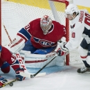 Montreal Canadiens goaltender Carey Price (31) makes a save against Washington Capitals' Marcus Johansson, right, as Canadiens' Mike Weaver defends during the third period of an NHL hockey preseason game Sunday, Sept. 28, 2014, in Montreal. The Associated