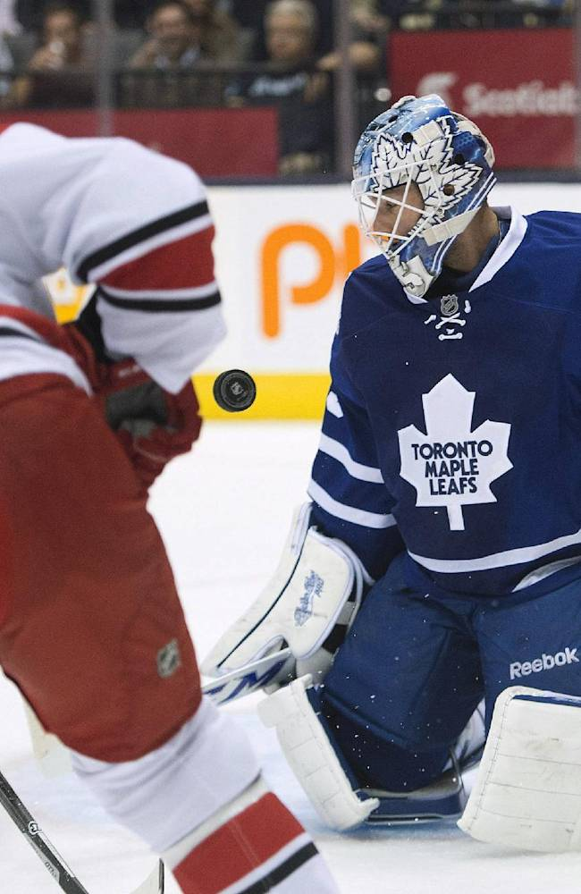 Toronto Maple Leafs goalie Jonathan Bernier, right, makes a save on a shot from Carolina Hurricanes forward Drayson Bowman (21) during the first period of an NHL hockey game in Toronto on Thursday, Oct. 17, 2013