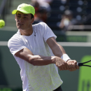 Bernard Tomic, of Australia, returns to Andy Murray, of Great Britain,during the Sony Open tennis tournament, Saturday, March 23, 2013, in Key Biscayne, Fla. (AP Photo/Lynne Sladky)