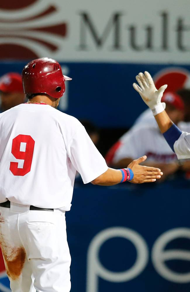Puerto Rico's outfielder Eddie Rosario, left, celebrates with his teammate Luis Figueroa after scoring a run against Venezuela during a Caribbean Series baseball game in Porlamar, Venezuela, Wednesday, Feb. 5, 2014