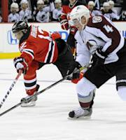 New Jersey Devils' Damien Brunnner, left, attempts to knock the puck away from Colorado Avalanche's Tyson Barrie during the second period of an NHL hockey game Monday, Feb. 3, 2014, in Newark, N.J. (AP Photo/Bill Kostroun)