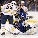 St. Louis Blues goaltender Brian Elliott, front right, reaches for the puck as he is pressured by Buffalo Sabres center Brian Flynn in second-period NHL hockey game action on Thursday, April 3, 2014, in St. Louis The Associated Press