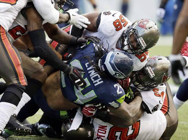 Seattle Seahawks running back Marshawn Lynch (24) is tackled by Tampa Bay Buccaneers' Dekoda Watson (56) during the second half of an NFL football game Sunday, Nov. 3, 2013, in Seattle