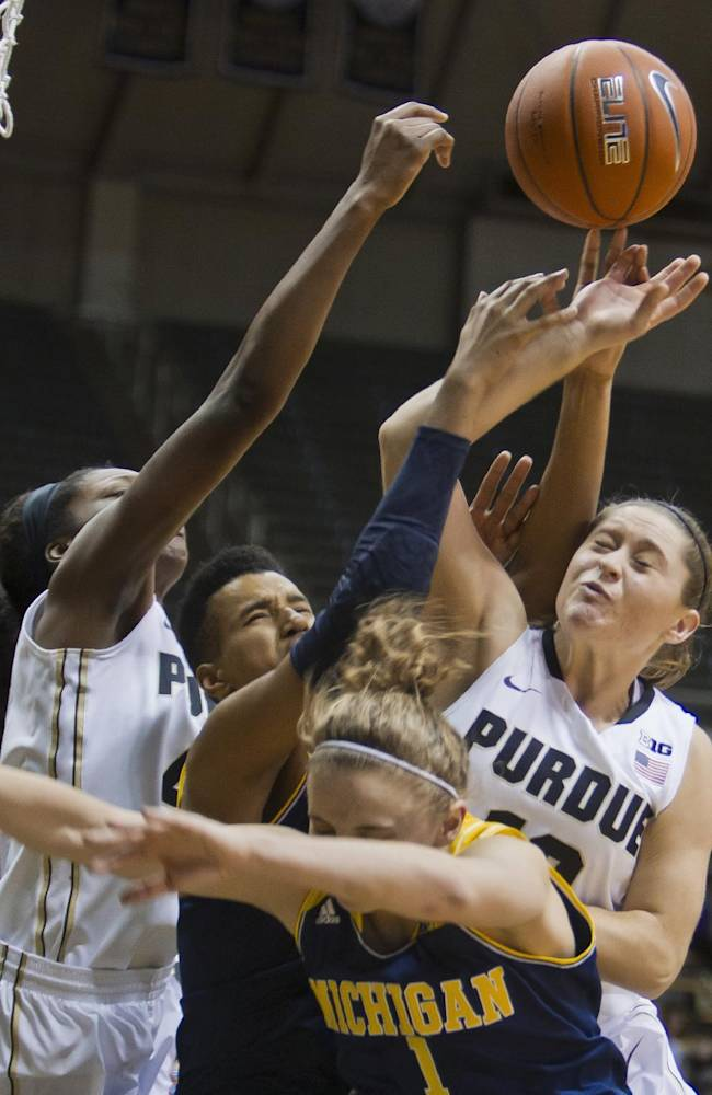 Purdue's Camille Redmon, left, and Hayden Camby and Michigan's Cyesha Goree and Madison Ristovski (1) go for a rebound during an NCAA college basketball game Wednesday, Jan. 15, 2014, in West Lafayette, Ind