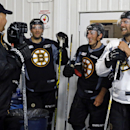 From left, Boston Bruins head coach Claude Julien chats with players Patrice Bergeron, Brad Marchand and Dennis Seidenberg (44) as they wait to take the ice during hockey training camp in Wilmington, Mass., Friday, Sept. 19, 2014 The Associated Press