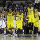 Michigan celebrates after beating Kansas 87-85 in overtime of a regional semifinal game in the NCAA college basketball tournament, Friday, March 29, 2013, in Arlington, Texas. (AP Photo/David J. Phillip)