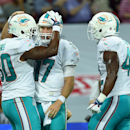 Miami Dolphins' Dion Sims, left, celebrates with Charles Clay, right, and Ryan Tannehill after scoring a touchdown during the NFL football game against Oakland Raiders at Wembley Stadium in London, Sunday, Sept. 28, 2014. The Associated Press