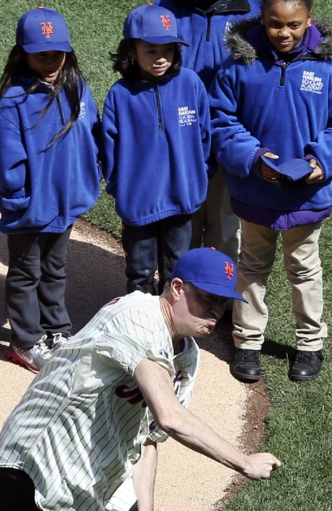 New York Mayor Bill de Blasio throws the ceremonial first pitch accompanied by children from the East Harlem Tutorial Program who were affected by the recent building collapse at the start of a baseball game between the New York Mets and Washington Nationals on opening day at Citi Field, Monday, March 31, 2014, in New York