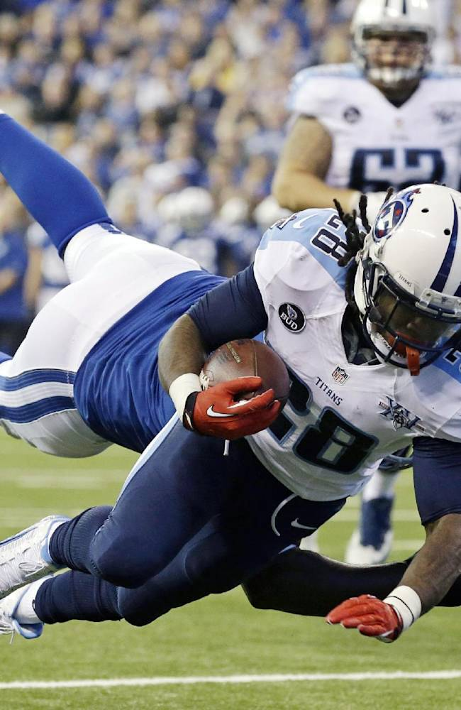 In this Dec. 1, 2013 file photo, Tennessee Titans' Chris Johnson (28) dives while being tackled by Indianapolis Colts' Cory Redding during the first half of an NFL football game in Indianapolis. The Titans have told Chris Johnson they are releasing him after six seasons to avoid paying the $8 million the running back is due in pay in 2014, and the final three seasons left on the $53.5 million contract he signed in September 2011. The Titans announced Johnson has been told he will be released Friday, April 4, 2014