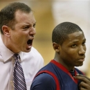 FILE - In this Feb. 8, 2010, file photo, Robert Morris' Karon Abraham, right, walks away as coach Mike Rice, left, shouts during a timeout in the first half of an NCAA college basketball game against Pittsburgh in Pittsburgh. A Robert Morris internal investigation into former basketball coach Rice found no evidence of the