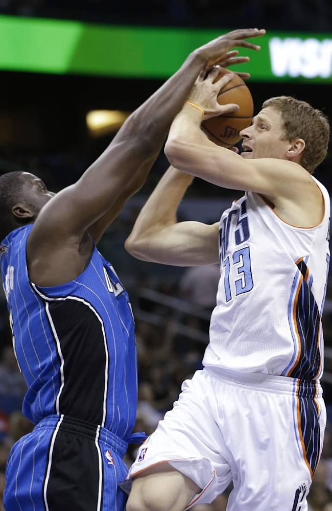 Orlando Magic's Victor Oladipo, left, ties up the ball as Charlotte Bobcats guard Luke Ridnour (13) goes up, resulting in a jump ball during the first half of an NBA basketball game in Orlando, Fla., Friday, March 28, 2014
