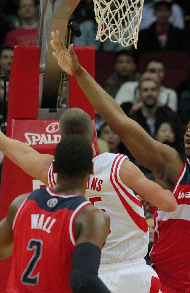 Washington Wizards center Kevin Serphin (13) defends as Houston Rockets forward Chandler Parsons, center, goes up to shoot and Wizards' John Wall looks on during the first half of an NBA basketball game in Houston, Wednesday, Feb. 12, 2014