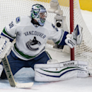 Vancouver Canucks goalie Ryan Miller keeps an eye on a flying puck as they face the Montreal Canadiens during second period NHL hockey action Tuesday, Dec, 9, 2014 in Montreal The Associated Press
