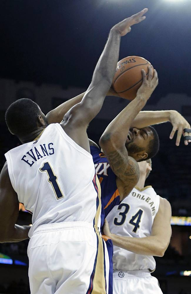 Phoenix Suns power forward Markieff Morris (11) is fouled as he goes to the basket between New Orleans Pelicans point guard Tyreke Evans (1) and center Greg Stiemsma (34) in the first half of an NBA basketball game in New Orleans, Tuesday, Nov. 5, 2013