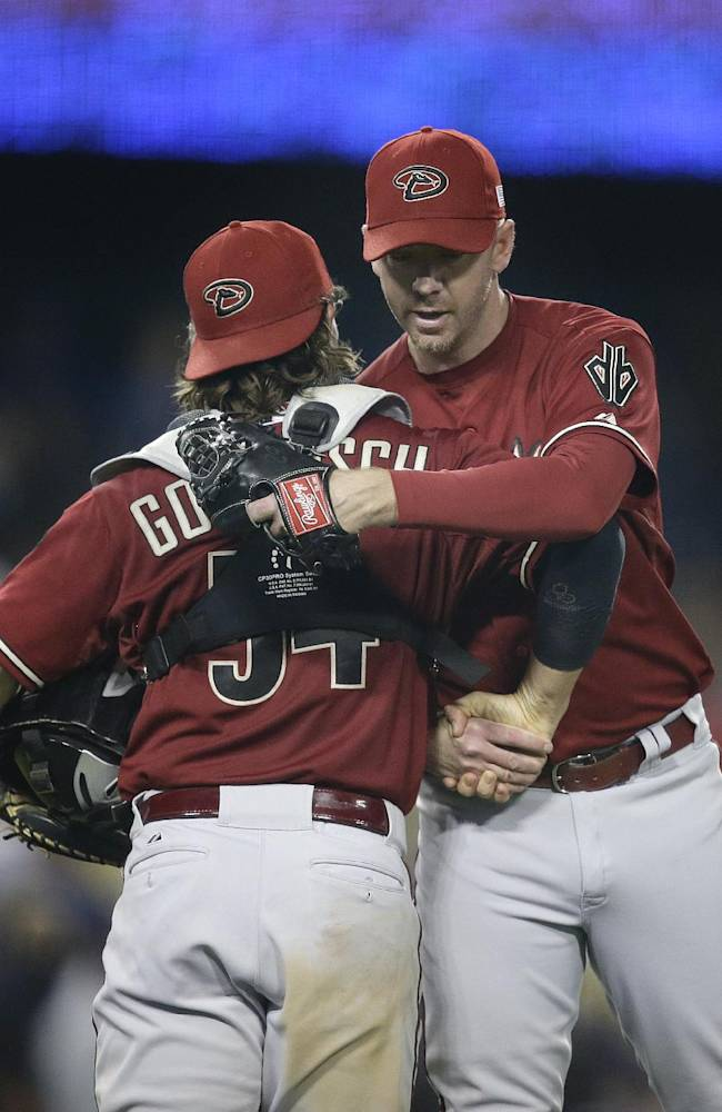 Arizona Diamondbacks relief pitcher Brad Ziegler, right, hugs catcher Tuffy Gosewisch as they celebrate their team's 4-1 win against the Los Angeles Dodgers after a baseball game on Wednesday, Sept. 11, 2013, in Los Angeles