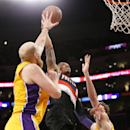Portland Trail Blazers guard Damian Lillard dunks between Los Angeles Lakers' Chris Kaman, left, and Pau Gasol during the first half of an NBA basketball game in Los Angeles, Tuesday, April 1, 2014 The Associated Press