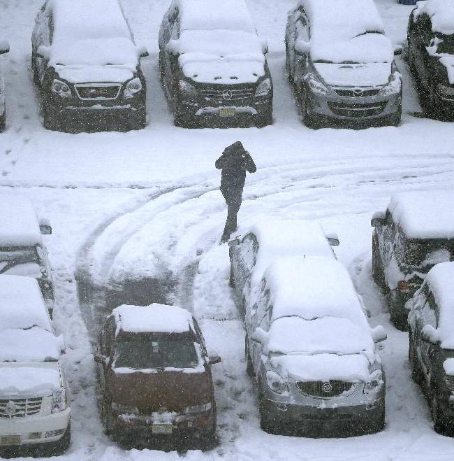 A person walks in a snow-covered parking lot outside Lincoln Financial Field during the second half of an NFL football game between the Philadelphia Eagles and the Detroit Lions, Sunday, Dec. 8, 2013, in Philadelphia