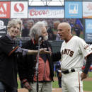 FILE - In this Oct. 14, 2014, file photo, from left to right Grateful Dead's Phil Lesh, and Bob Weir with San Francisco Giants' Tim Flannery sing the national anthem before Game 3 of the National League baseball championship series between the San Francisco Giants and the St. Louis Cardinals in San Francisco. The Giants have lost their third base coach in addition to their third baseman. On the day Pablo Sandoval finalized his reached agreement with the Boston Red Sox, third base coach Tim Flannery announced he is retiring from the Giants. (AP Photo/David J. Phillip, File)