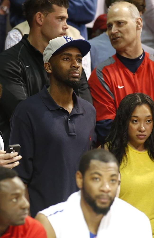 Former SMU player Quenton Ross,, center in Kansas City hat, who was falsely reported dead in NY earlier in the day, watches the SMU vs LSU game from behind the SMU bench during the second half of an NCAA college basketball game in the second round of the NIT Monday, March 24, 2014, in Dallas, Texas