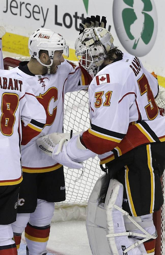 Calgary Flames' Mark Cundari (42) congratulates goalie Karri Ramo (31), of Finland, after they defeated the New Jersey Devils in an NHL hockey game in Newark, N.J., Monday, April 7, 2014. The Flames won 1-0