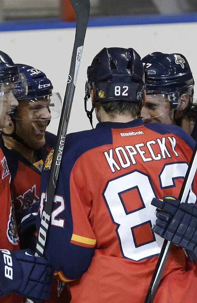Florida Panthers right wing Kris Versteeg, second from left, is congratulated by Aleksander Barkov (16), Tomas Kopecky (82), Dmitry Kulikov (7) and another player after scoring a goal in the third period during a preseason NHL hockey game against the Tampa Bay Lightning, Saturday, Sept. 28, 2013, in Sunrise, Fla. The Panthers defeated the Lightning 5-3