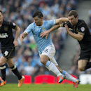Manchester City's Sergio Aguero, center, keeps Wigan's James McArthur at bay during their English FA Cup quarterfinal soccer match at the Etihad Stadium, Manchester, England, Sunday, March 9, 2014