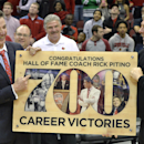 Louisville head coach Rick Pitino, left, laughs at one of the photos of himself as University of Louisville Athletic Director Tom Jurich looks on as they celebrate the 700th win of his career Wednesday, Nov. 26, 2014, in Louisville, Ky. (AP Photo/Timothy D. Easley)