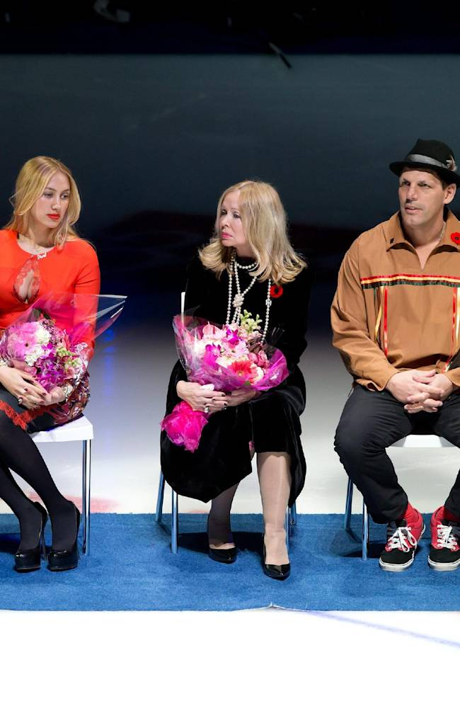 From left to right, retired Vancouver Canucks forward Pavel Bure, of Russia, sits with his wife Alina Khasanova, his mother Tatiana Bure, former teammate Gino Odjick and Pat Quinn during a ceremony where his No. 10 was retired before the Canucks' NHL hockey game against the Toronto Maple Leafs in Vancouver, British Columbia, Saturday, Nov. 2, 2013