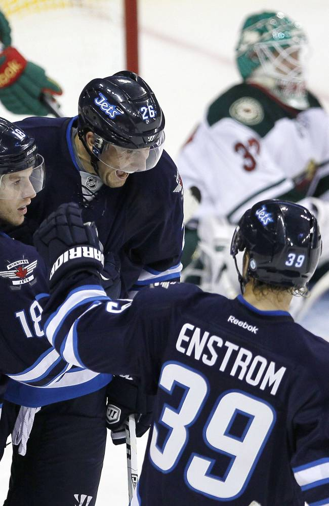Winnipeg Jets' Bryan Little (18), Blake Wheeler (26) and Toby Enstrom (39) celebrate Little's goal against Minnesota Wild goaltender Josh Harding during first-period preseason NHL hocky game action in Winnipeg, Manitoba, Thursday, Sept. 19, 2013