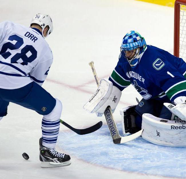 Toronto Maple Leafs' Colton Orr, left, loses control of the puck and fails to get a shot on Vancouver Canucks' goalie Roberto Luongo during the first period of an NHL hockey game in Vancouver, British Columbia, on Saturday, Nov. 2, 2013