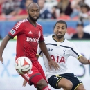 Toronto FC's Collen Warner, left, and Tottenham Hotspur's Aaron Lennon battle for the ball during the first half of a friendly soccer match in Toronto on Wednesday, July 23, 2014